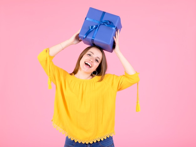 Mulher jovem feliz levando presente sobre a cabeça dela contra o fundo rosa