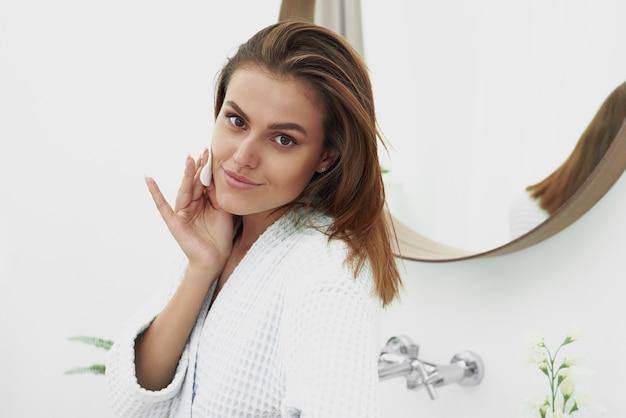 Mulher jovem feliz limpando o rosto com almofadas de algodão no banheiro