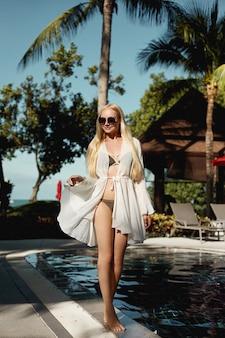 Mulher jovem feliz modelo de biquíni se passando perto da piscina no território do luxuoso re ...