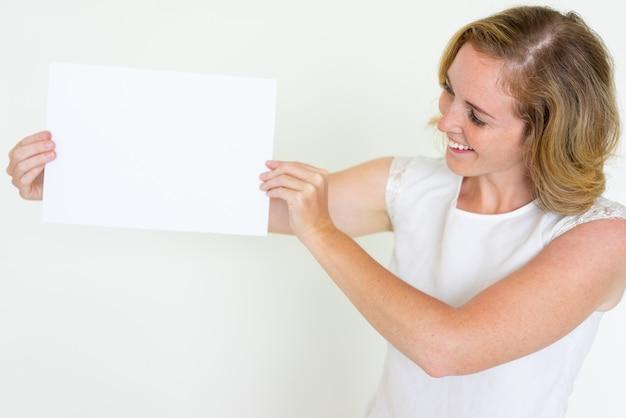 Mulher jovem feliz, mostrando a folha de papel em branco