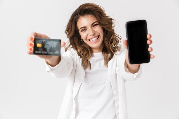 Mulher jovem feliz mostrando cartão de crédito de plástico e celular com tela em branco isolado