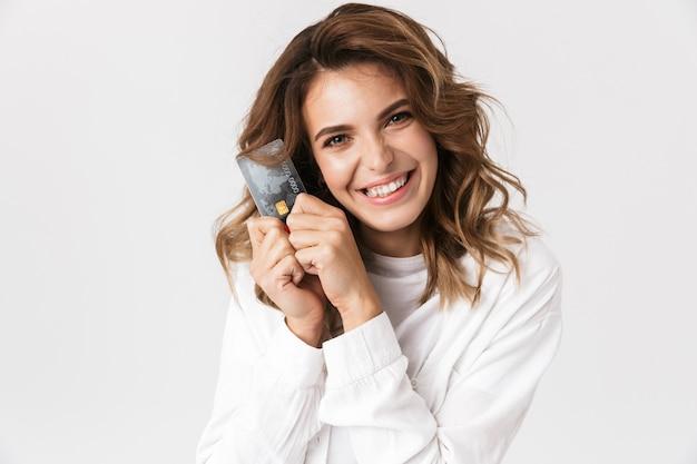 Mulher jovem feliz mostrando cartão de crédito de plástico isolado