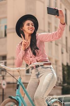 Mulher jovem feliz mostrando gesto de paz para selfie na bicicleta