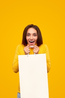 Mulher jovem feliz mostrando um saco de papel vazio e gritando de empolgação durante as compras