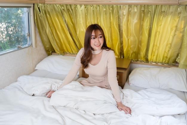 Mulher jovem feliz na cama de um trailer trailer trailer