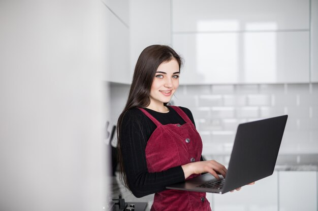 Mulher jovem feliz na cozinha lendo ele notícias em seu laptop