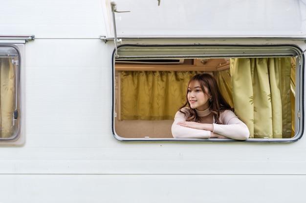 Mulher jovem feliz na janela de um trailer trailer van motorhome
