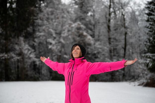 Mulher jovem feliz na jaqueta de inverno rosa em pé na bela natureza nevada com os braços amplamente abertos.