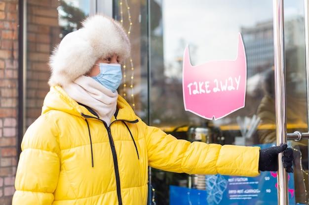Mulher jovem feliz na porta do restaurante em um dia frio de inverno, letras, comida para viagem.