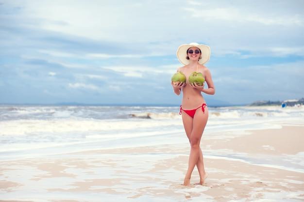 Mulher jovem feliz na praia com uma bebida de coco