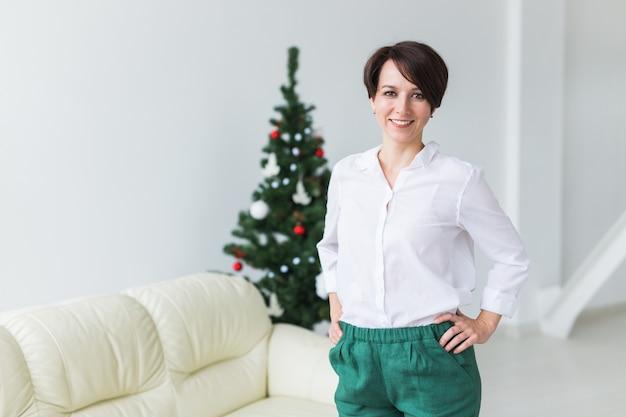 Mulher jovem feliz na sala de estar com árvore de natal.