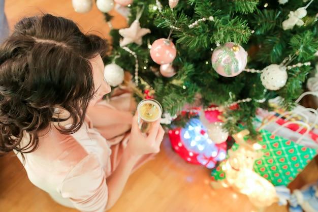 Mulher jovem feliz na véspera de natal perto de abeto festivo