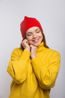Mulher jovem feliz no chapéu de malha vermelho