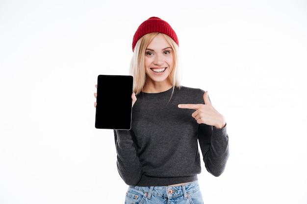 Mulher jovem feliz no dedo apontando chapéu no tablet de tela em branco