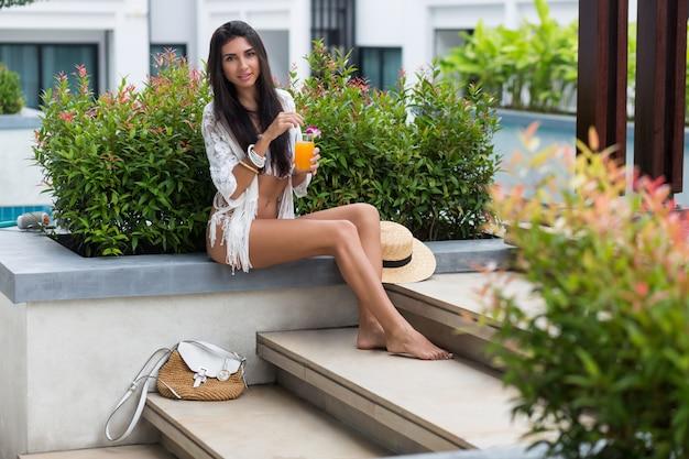 Mulher jovem feliz no elegante boho white beachwear, sentado perto da piscina tropical em um hotel de luxo e desfrutando de um coquetel de laranja ou suco.