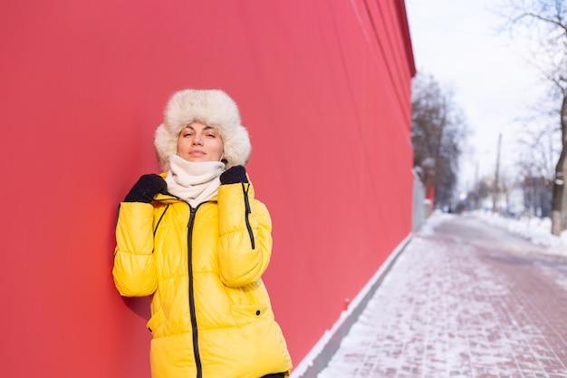 Mulher jovem feliz no fundo de uma parede vermelha com roupas quentes em um dia ensolarado de inverno