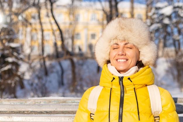 Mulher jovem feliz no inverno com roupas quentes em um parque nevado em um dia ensolarado se senta nos bancos e aproveita o ar fresco e o café sozinha