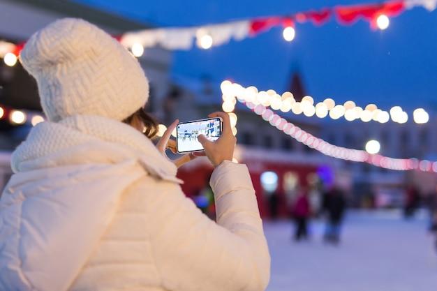 Mulher jovem feliz no inverno na pista de gelo tirando fotos no smartphone.