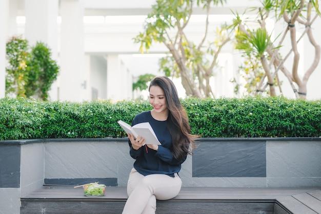 Mulher jovem feliz no parque no dia ensolarado de verão lendo livro. menina bonita alegre em um lindo dia.