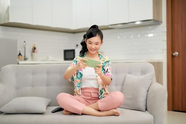Mulher jovem feliz no sofá segurando uma loja online de smartphone ou verifique o aplicativo móvel ou a mídia social
