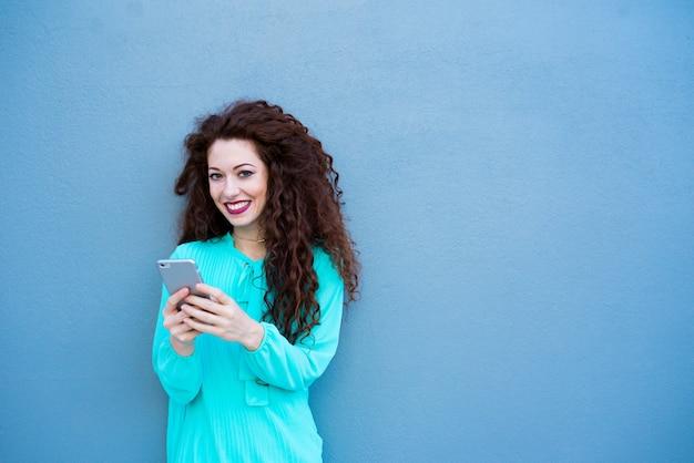 Mulher jovem feliz no telefone celular em uma parede azul