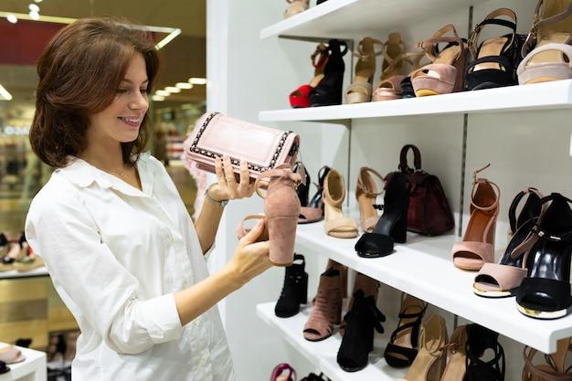 Mulher jovem feliz olha elegante sapato de salto nu no fundo do sapato