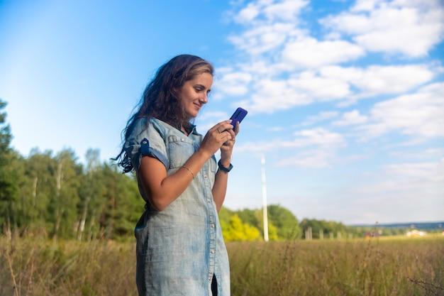 Mulher jovem feliz olhando para smartphone no fundo da natureza em dia ensolarado