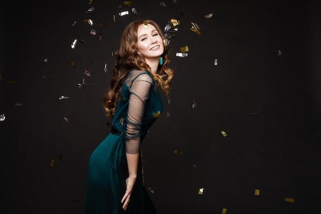 Mulher jovem feliz olhando surpreendentemente enquanto confetes dourados caindo