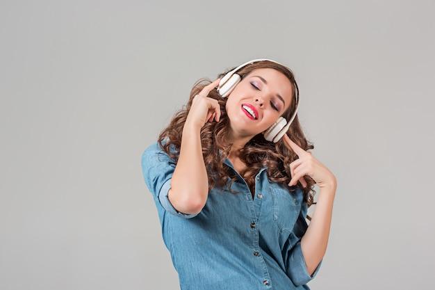 Mulher jovem feliz ouvindo música com fones de ouvido. retrato isolado em cinza
