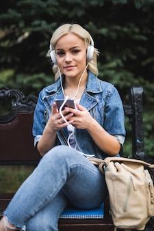 Mulher jovem feliz ouvindo música em fones de ouvido e usando o smartphone enquanto está sentado no banco da cidade