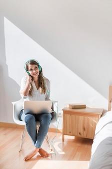 Mulher jovem feliz ouvindo música no laptop