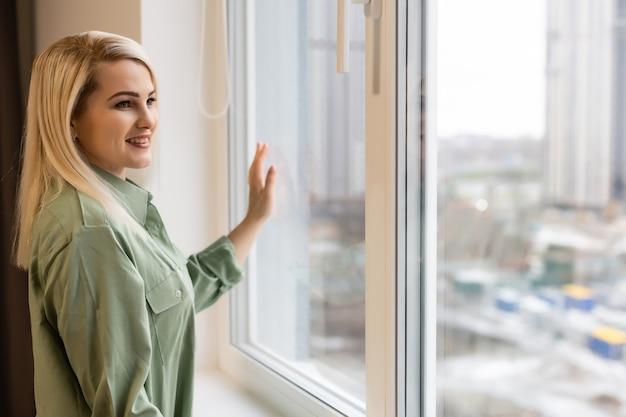 Mulher jovem feliz perto da janela respirar ar fresco exercício de alongamento no quarto, sorrindo, menina milenar radiante, bem-vinda, nova manhã ensolarada em casa ou hotel, otimismo, conceito de felicidade