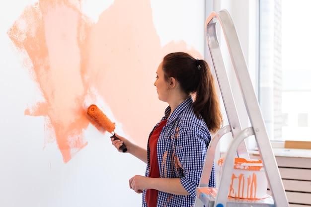 Mulher jovem feliz pintando a parede em seu novo apartamento. conceito de renovação, redecoração e reparação.