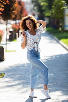 Mulher jovem feliz posando ao ar livre