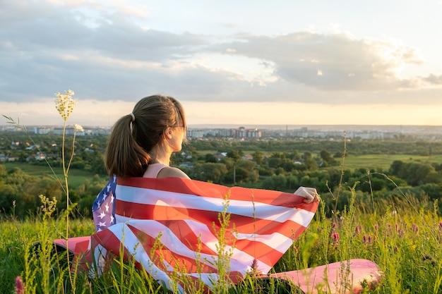 Mulher jovem feliz posando com a bandeira nacional dos eua em pé ao ar livre ao pôr do sol. menina positiva comemorando o dia da independência dos estados unidos. dia internacional do conceito de democracia.