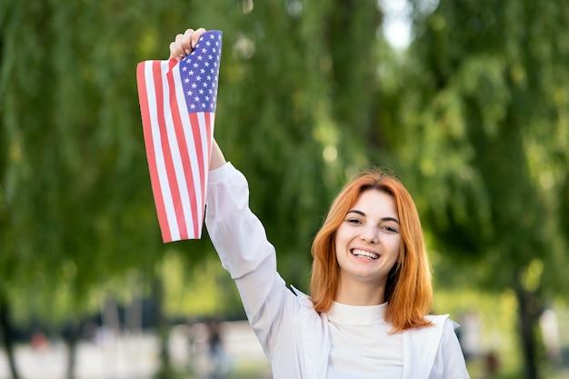 Mulher jovem feliz posando com a bandeira nacional dos eua, segurando-o na mão estendida em pé ao ar livre no parque de verão