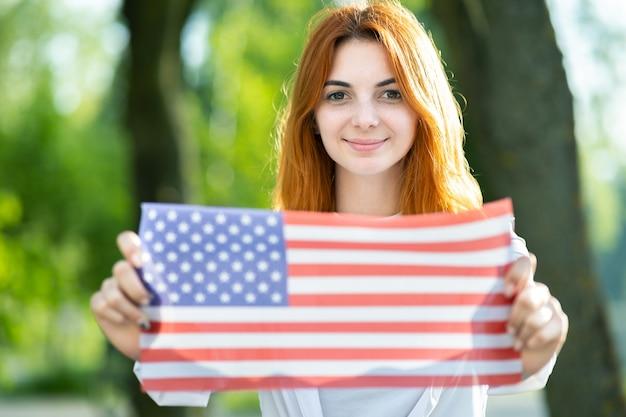 Mulher jovem feliz posando com a bandeira nacional dos eua, segurando-o nas mãos estendidas em pé ao ar livre no parque de verão.
