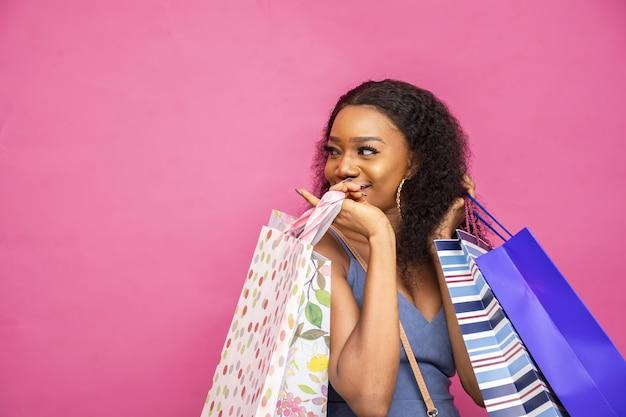 Mulher jovem feliz posando com sacolas de compras isoladas em uma parede rosa