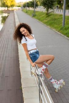 Mulher jovem feliz posando do lado de fora com patins