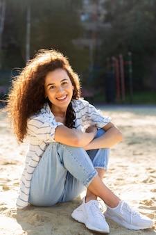 Mulher jovem feliz posando sentada na areia