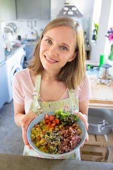 Mulher jovem feliz positiva posando com prato de vegetais caseiro em sua cozinha, mostrando a tigela, olhando para a câmera e sorrindo. tiro vertical, ângulo alto. conceito de alimentação saudável