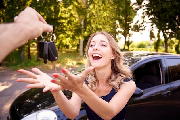 Mulher jovem feliz recebe as chaves do carro.