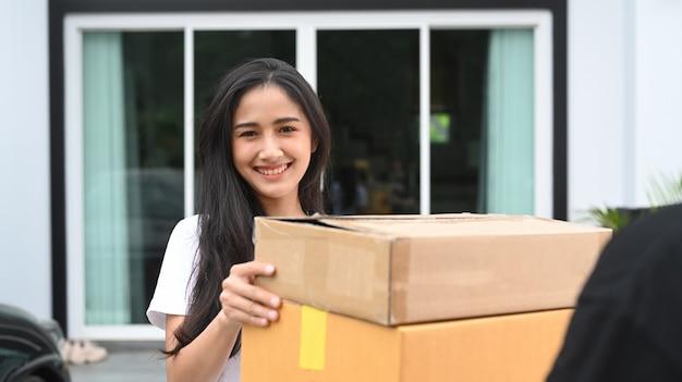 Mulher jovem feliz recebendo a caixa do pacote do entregador.