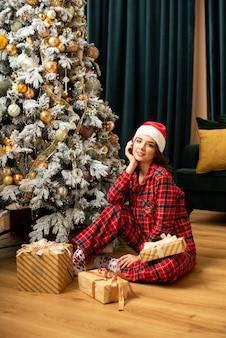 Mulher jovem feliz relaxando perto de árvore de natal. ela está sentada perto de presentes e presentes. fortuna ouro e tidewater green. pantone 2021