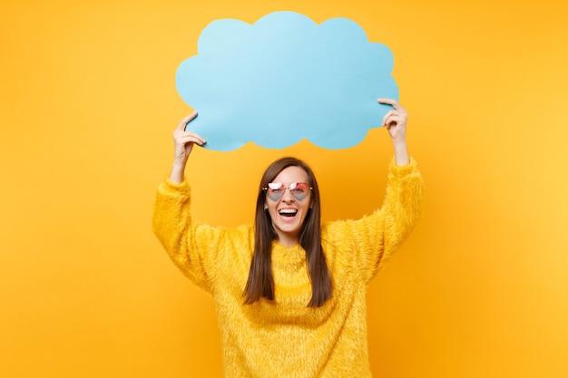 Mulher jovem feliz rindo em óculos de coração segurando vazio azul em branco say nuvem, balão de fala isolado em fundo amarelo brilhante. emoções sinceras de pessoas, conceito de estilo de vida. área de publicidade.