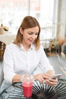Mulher jovem feliz rolando no smartphone enquanto procura um vídeo online curioso durante o descanso no café depois de fazer compras no shopping