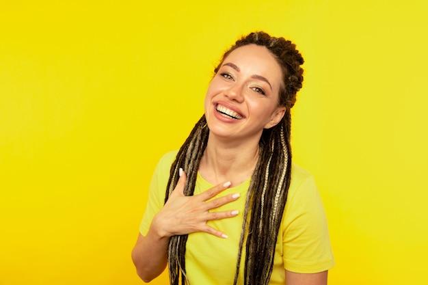 Mulher jovem feliz saiu na parede amarela.