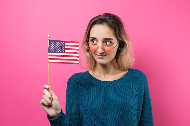 Mulher jovem feliz segurando a bandeira americana contra um fundo rosa estúdio