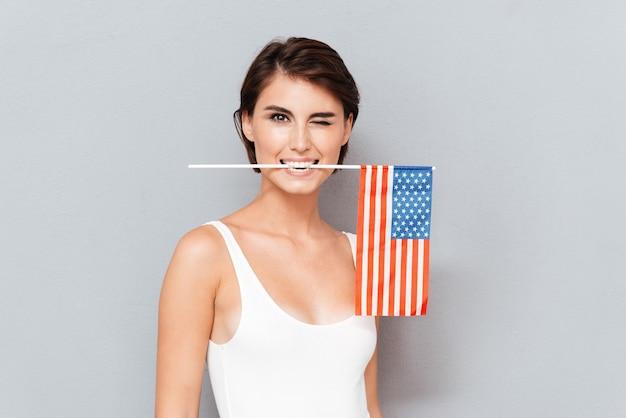 Mulher jovem feliz segurando a bandeira dos eua entre os dentes e piscando sobre um fundo cinza