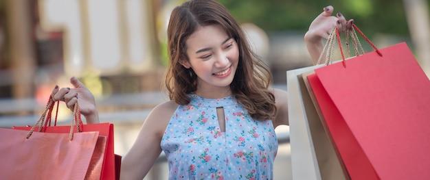 Mulher jovem feliz, segurando a sacola de compras com a desfrutar.